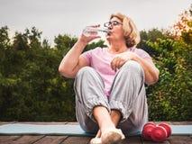 Donna sveglia e adulta che fa esercizio nel parco su un fondo di cielo blu ed in alberi verdi un chiaro, giorno soleggiato Concet fotografia stock