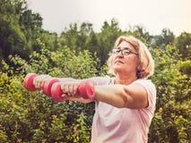 Donna sveglia e adulta che fa gli esercizi con le teste di legno rosa nel parco contro il cielo blu e gli alberi verdi in un chia fotografia stock