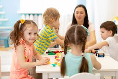 Donna sveglia e bambini che giocano i giocattoli educativi all'asilo o alla stanza della scuola materna fotografie stock libere da diritti