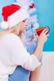 Donna in tè o caffè bevente del cappello di natale di Santa Fotografie Stock Libere da Diritti