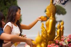Donna tailandese che bagna la statua del Buddha Immagine Stock