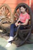 Donna tailandese che si siede sulla sedia del cartwheel Fotografia Stock