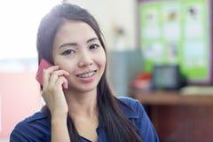 Donna tailandese che usando cellulare Fotografia Stock