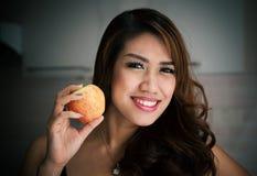 Donna tailandese felice che sorride con Apple Immagine Stock