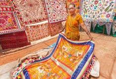 Donna tappeti commerciali e coperte di un oggetto d'antiquariato per la casa durante il giorno del mercato in città indiana Immagini Stock Libere da Diritti