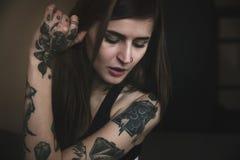 Donna tatuata giovani con le pose lunghe dei capelli Immagini Stock Libere da Diritti