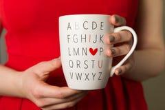 Donna in tazza da caffè rossa della tenuta del vestito, ti amo, tazza di giorno di biglietti di S. Valentino immagini stock