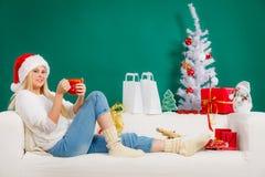 Donna in tazza di festa della tenuta del cappello di Santa, bevente Fotografia Stock