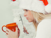 Donna in tazza di festa della tenuta del cappello di Santa, bevente Fotografia Stock Libera da Diritti