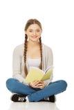 Donna teenager che si siede con il suo taccuino Fotografie Stock