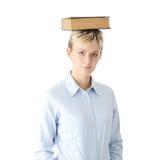 Donna teenager dell'allievo con il libro sulla testa Immagine Stock