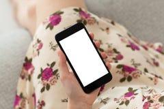 Donna in telefono della tenuta della stampa floreale del vestito con lo schermo isolato fotografia stock