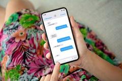 Donna in telefono variopinto della tenuta del vestito con il messaggero del app immagini stock libere da diritti