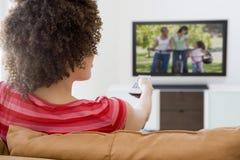 Donna in televisione di sorveglianza del salone immagini stock libere da diritti