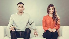Donna timida ed uomo che si siedono sul sofà Immagini Stock