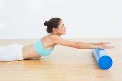 Donna tonificata che fa allungando esercizio nello studio di forma fisica Immagine Stock Libera da Diritti