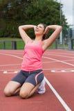Donna tonificata che fa allungando esercizio sulla pista corrente Immagini Stock Libere da Diritti