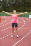 Donna tonificata che fa allungando esercizio sulla pista corrente Fotografie Stock Libere da Diritti