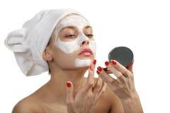 Donna in tovagliolo che fa mascherina cosmetica Immagine Stock