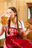 donna in Tracht bavarese in ristorante o in pub Fotografie Stock Libere da Diritti