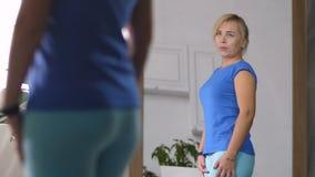 Donna triste che esamina specchio dopo il guadagno del peso video d archivio