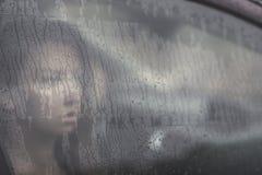 Donna triste che guarda attraverso la finestra con goccia di pioggia nell'automobile Fronte di giovane femmina dietro la finestra Immagini Stock Libere da Diritti