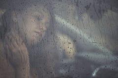 Donna triste che guarda attraverso la finestra con goccia di pioggia nell'automobile Fronte di giovane femmina dietro la finestra Immagine Stock