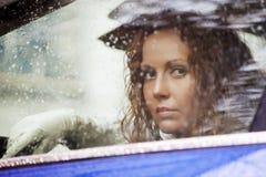 Donna triste che guarda fuori la finestra di automobile Immagini Stock Libere da Diritti