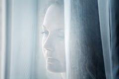 Donna triste che osserva fuori la finestra immagini stock