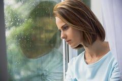Donna triste che si siede all'interno mentre piovendo Fotografie Stock