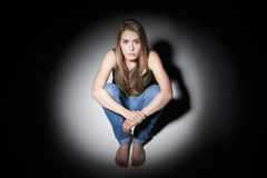Donna triste che si siede nello stagno di luce Fotografie Stock