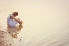 Donna triste che si siede sul tramonto della spiaggia deludente, tristezza Immagine Stock