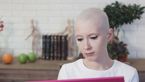 Donna triste che soffre dal cancro che esamina la foto della sua famiglia video d archivio