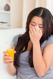 Donna triste con il succo di arancia sul sofà Fotografia Stock