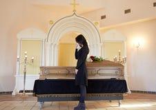 Donna triste con la bara al funerale in chiesa immagini stock