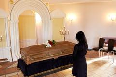 Donna triste con la bara al funerale in chiesa fotografia stock