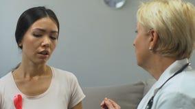 Donna triste con medico di visita del nastro rosa, discutente i sintomi di cancro al seno stock footage