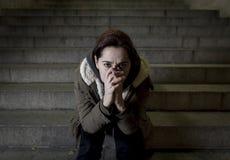 Donna triste da solo sulla depressione di sofferenza della scala del sottopassaggio della via che sembra guardante malato ed impo Fotografie Stock