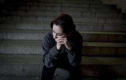 Donna triste da solo sulla depressione di sofferenza della scala del sottopassaggio della via che sembra guardante malato ed impo Fotografia Stock Libera da Diritti