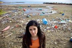 Donna triste davanti allo scarico ed alla spiaggia sporca Fotografia Stock