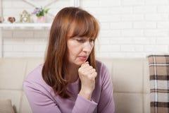 Donna triste di medio evo che si siede su un sofà nel salone menopause immagine stock