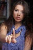 Donna triste dietro la finestra bagnata fotografia stock libera da diritti