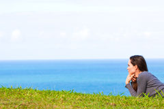 Donna triste e depressa che si trova nell'erba verde Fotografia Stock Libera da Diritti