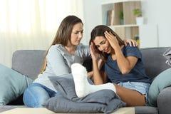 Donna triste ed amico disabili che la confortano Immagine Stock