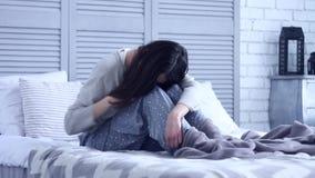 Donna triste infruttuosa che si siede alla camera da letto grigia sul letto video d archivio