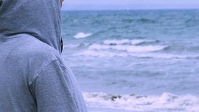 Donna triste in maglia con cappuccio che cammina da solo sulla spiaggia vuota, esaminante orizzonte, depressione stock footage