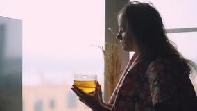 Donna triste malata in plaid che si siede su un tè bevente del davanzale della finestra e su uno sguardo premuroso nella finestra archivi video