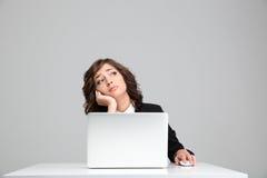 Donna triste premurosa di affari che sogna seduta al computer portatile immagini stock