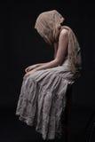 Donna triste in sciarpa che si siede con il fronte nascosto immagine stock libera da diritti