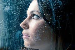 Donna triste sulla finestra nella pioggia Fotografie Stock